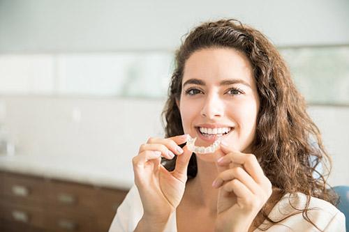 Jeune femme tenant dans ses mains une gouttière dentaire invisible